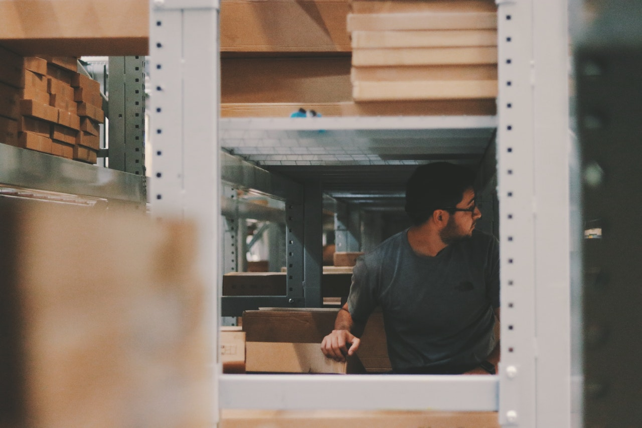 man working in shelves of packages